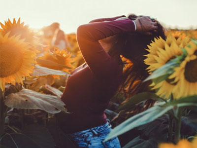 girl in sun and sunflowers